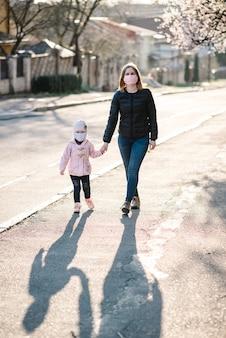 コロナウイルスと大気汚染の概念。小さな女の子とマスクを身に着けている母親が通りを歩きます。パンデミックウイルスの症状。屋外の子供と家族。
