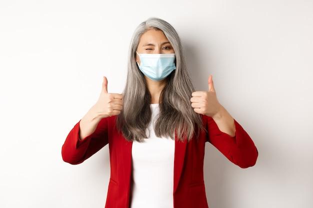 コロナウイルスとビジネスコンセプト。フェイスマスクのアジアの女性起業家は陽気に見え、承認で親指を立てて、白い背景を示しています