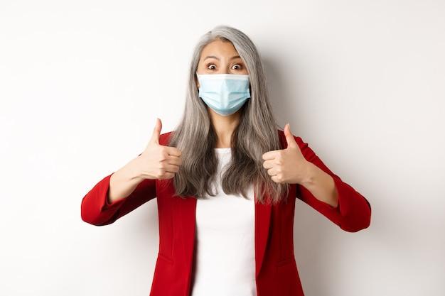 コロナウイルスとビジネスコンセプト。陽気に見えるフェイスマスクのアジアの女性マネージャー、承認、白い背景の親指を示しています