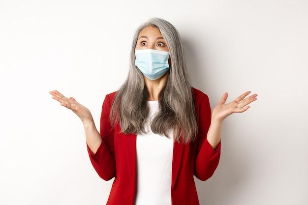 コロナウイルスとビジネスコンセプト。フェイスマスクで驚いたアジアの実業家、手を横に広げ、左上隅、白い背景でショックを受けて見つめる