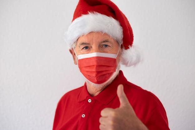 コロナウイルスとクリスマス2020。親指を上にしてサージカルマスクを身に着けているサンタの帽子をかぶった老人の肖像画。白い背景の上の赤い色