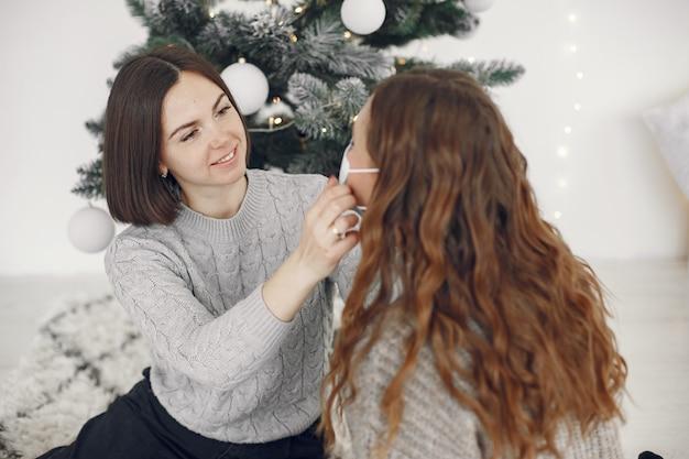 코로나 바이러스와 크리스마스 개념. 여자는 마스크를 쓰고 그녀의 친구를 도와줍니다.