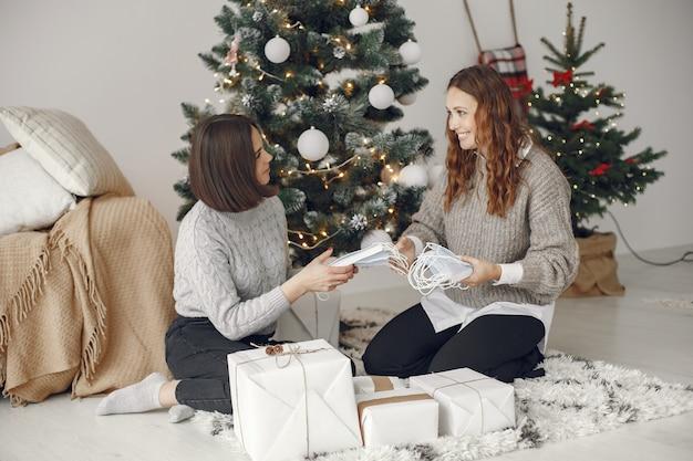 코로나 바이러스와 크리스마스 개념. 집에서 여자. 회색 스웨터에 아가씨.