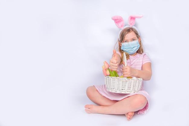 コロナウイルスとイースター休暇。バニーの耳を持つ保護医療マスクのかわいい女の子。イースターバナーの背景。イースターエッグと春の花のバスケット