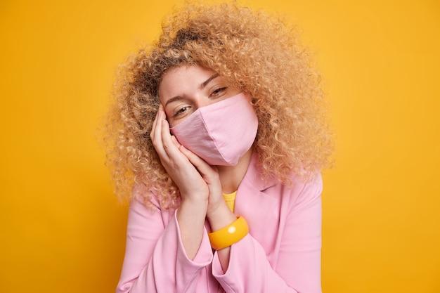 코로나 바이러스 및 격리 시간 개념. 덥수룩 한 곱슬 머리를 가진 아름 다운 젊은 여자는 노란색 벽 위에 고립 된 공식적인 옷을 입고 바이러스를 방지하기 위해 공공 장소에서 보호 마스크를 착용