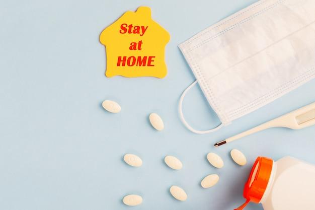 コロナウイルスと在宅のコンセプト。医療用フェイスマスク、体温計、薬