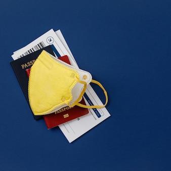 コロナウイルスと旅行の概念。パスポート、飛行機のチケット、医療用マスクの平置き。