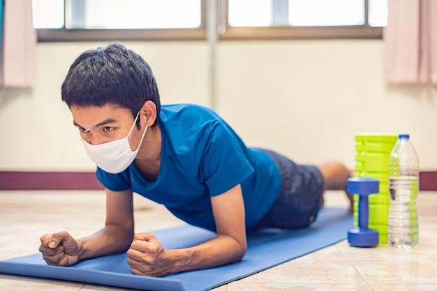 コロナウイルス、アジア人男性がマスクを着用し、自宅の部屋で1人でcovid-19を防止するために運動します。自宅からのトレーニング、自宅からのエクササイズ。