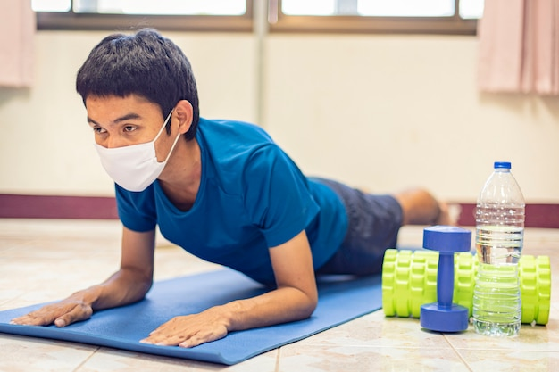Coronavirus, asian man wear a mask and exercise alone in room at home to preventing covid-19. workout from home, exercise from home.