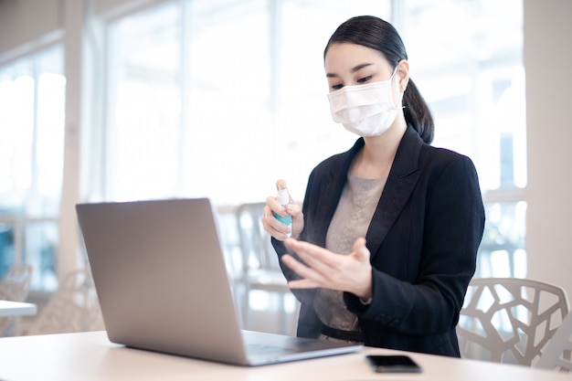 코로나 바이러스. 보호 마스크를 착용하는 가정에서 일하는 비즈니스 여자. 보호 마스크를 착용하는 코로나 바이러스에 대 한 격리에서 비즈니스 여자. 재택 근무. 알코올 스프레이로 손을 청소합니다.