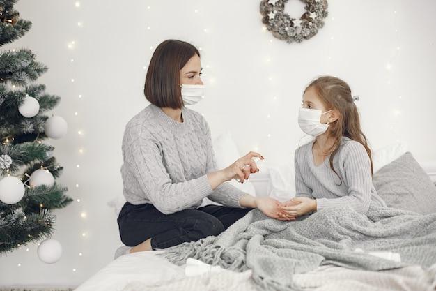 Coronavirus in un bambino. madre con figlia. bambino sdraiato in un letto. donna in una maschera medica.