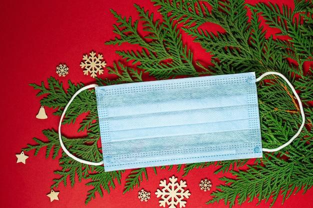 Коронавирус рождественский фон. маска для лица с праздничными украшениями и зелеными еловыми ветками на красном фоне. рождество или новый год концепция. плоская планировка