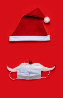 Coronavirus christmas background. santa claus hat with face mask on a red background.