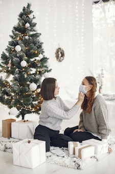 Coronavirus and christmas concept. woman helps her friend wearing a mask.