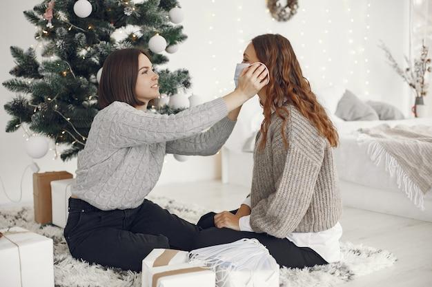 Coronavirus e concetto di natale. la donna aiuta la sua amica che indossa una maschera.