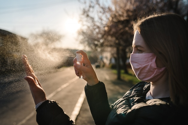 Coronavirus. cleaning hands with sanitizer spray in city. woman wearing medical protective mask on street. sanitizer to prevent coronavirus, covid-19, flu. spray bottle. virus and illness protection.