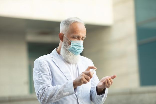 Коронавирус. очистка рук дезинфицирующим спреем в городе