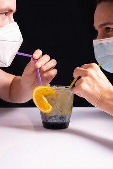 Коктейль из коронавируса. крупный план парня с девушкой в защитных масках, пьющих коктейль из соломинок из стакана