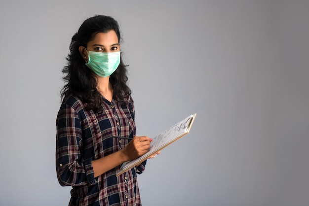 혈액 검사를위한 코로나 바이러스 개념. 코로나 바이러스 테스트를 위해 의료 테스트 양식을 읽거나 채우는 어린 소녀.