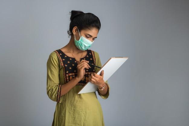 혈액 검사를위한 코로나 바이러스 개념. 코로나 바이러스 테스트를위한 의료 테스트 양식을 읽거나 채우는 어린 소녀.