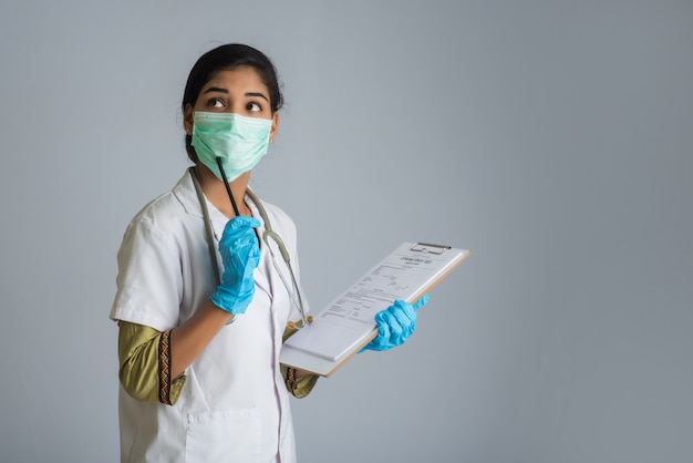 혈액 검사를위한 코로나 바이러스 개념. 코로나 바이러스 테스트를 위해 의료 테스트 양식을 읽거나 채우는 젊은 여자 의사.