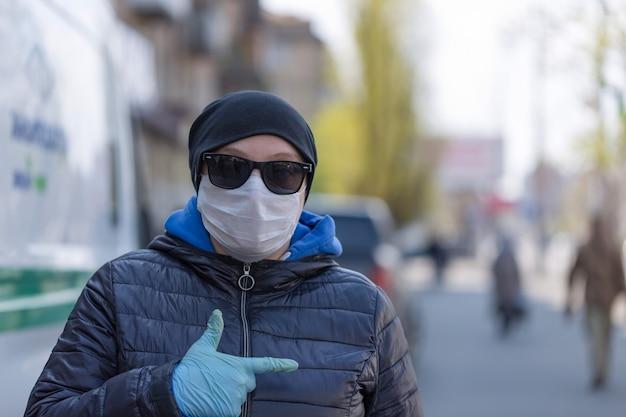 コロナウイルスの概念病気からの保護マスクと保護手袋を着用している女の子が通りにいます