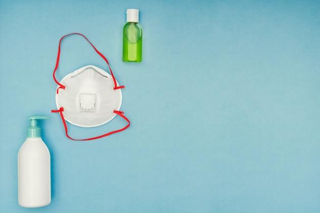 コロナウイルス、covid-19。防腐剤ジェル、液体私たち、青色の背景に保護マスク