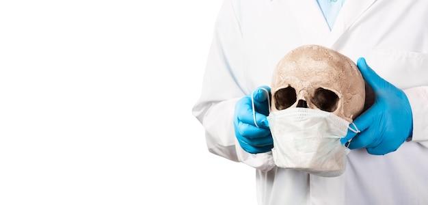 コロナウイルスcovid-19の概念。白い背景で隔離のマスクと人間の頭蓋骨を保持しているゴム手袋の医師。テキスト用の空き容量。