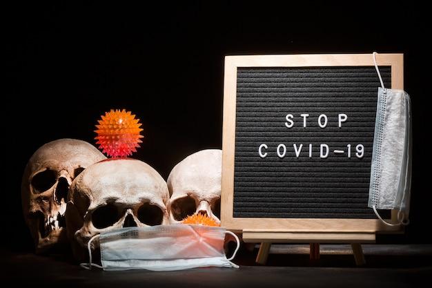 コロナウイルスcovid-19の概念。暗い背景に対してstopcovid-19という言葉で文字盤の近くにマスクとウイルスモデルを持つ人間の頭蓋骨。