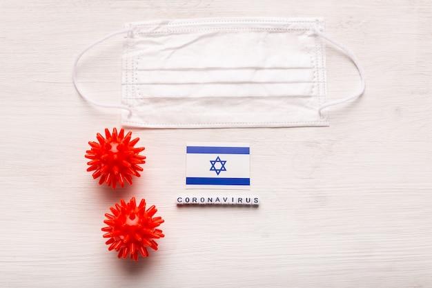 Концепция коронавируса ковид-19. вид сверху защитная дыхательная маска и флаг израиля. новая китайская коронавирусная вспышка.