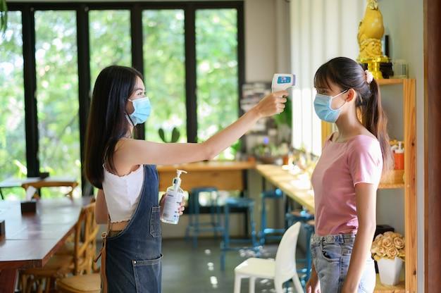 Coronavirus covid-19コンセプト、サーモスキャンまたはサーモメーター銃でコロナウイルスをスクリーニングするマスクを着ている女性