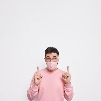 Concetto di coronavirus covid 19. il giovane indossa una maschera igienica per prevenire malattie contagiose in un maglione rosa casual ha una malattia respiratoria che indica verso l'alto su uno spazio vuoto contro il muro bianco