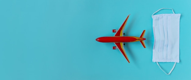 코로나바이러스 covid-19 비행 상황 개념. 카피스페이스, 플랫레이, 배너가 있는 밝은 파란색 배경에 얼굴 마스크와 비행기 빨간 장난감