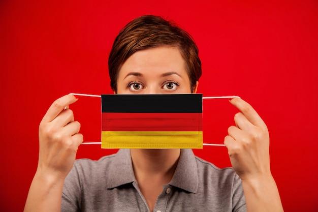 ドイツのコロナウイルスcovid-19。ドイツの旗のイメージを持つ医療防護マスクの女性。
