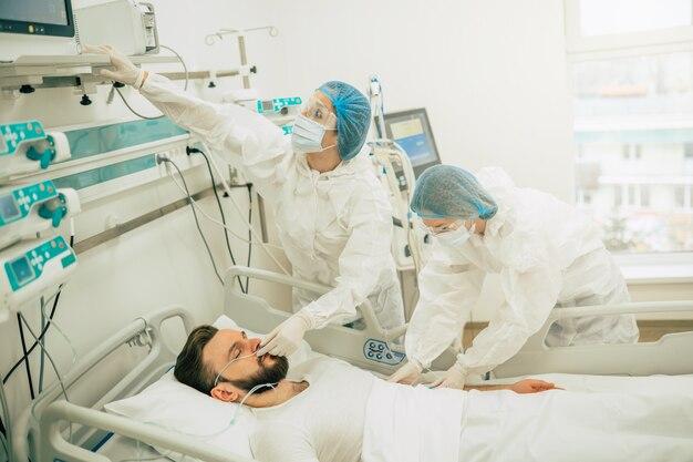 コロナウイルスcovid-19感染患者が病院の検疫病棟におり、医師が彼の病気の治療を行っている間、防護服を着ています。