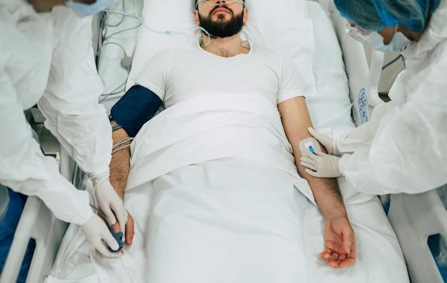 Пациент, инфицированный коронавирусом covid-19, в карантинной палате больницы с врачами в защитных костюмах, пока они лечат его