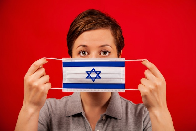 Coronavirus covid-19 in israel. woman in medical protective mask with the image of the flag of israel.