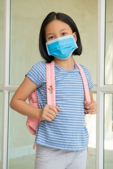 Coronavirus covid-19.online education. little asian kid girl wearing face mask show thumbs up for thank you doctor, happy at home. child with face mask going back to school after covid-19 quarantine