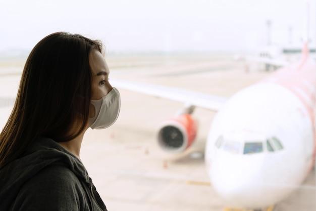 Молодая азиатская женщина с защитой стороны хирургической маски на крупном аэропорте. концепция здравоохранения и защиты, концепция coronavirus / covid-19 и загрязнение воздуха pm2.5.