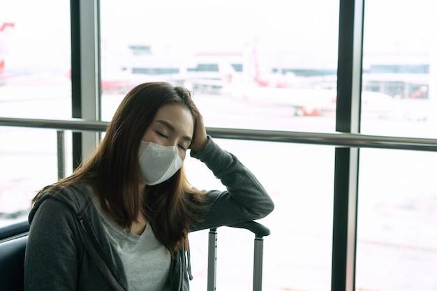 Больная молодая азиатская женщина с защитой стороны хирургической маски сидя на крупном аэропорте. концепция защиты coronavirus / covid-19 и загрязнения воздуха pm2.5.