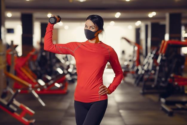 コロナウイルスcovid-19予防、ダンベルを保持している医療マスクを持つフィットネス少女。ウイルスとの戦い。