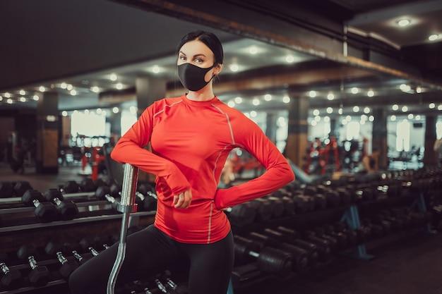 Профилактика коронавируса covid-19, фитнес-девушка с медицинской маской, держащая гантель