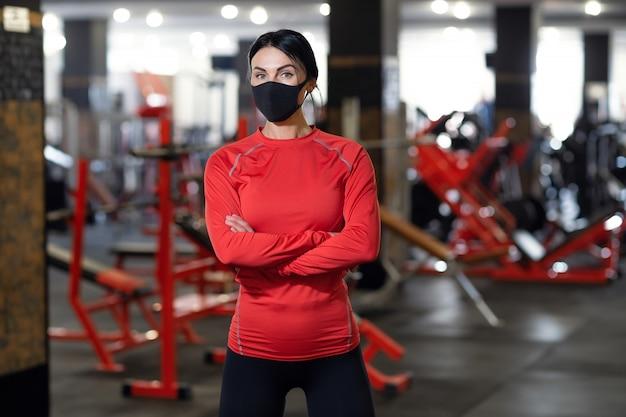 コロナウイルスcovid-19予防、ジムでポーズをとって医療マスクを持つフィットネス女の子。ウイルスとの戦い。