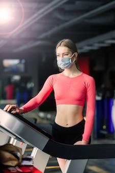 コロナウイルスcovid-19予防、ジムでポーズをとる医療マスクを持つフィットネスの女の子。ウイルスとの戦い。