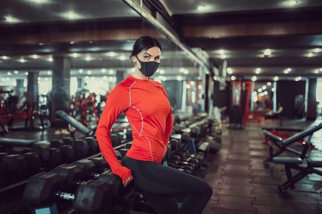 Профилактика коронавируса covid-19, фитнес-девушка с медицинской маской позирует в тренажерном зале