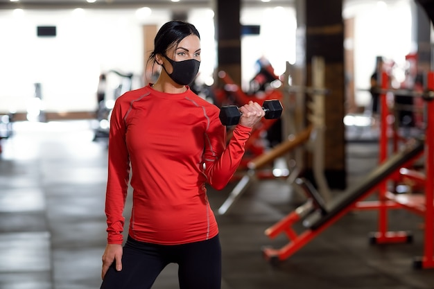 Coronavirus covid-19 prevention, fitness girl with a medical mask holding a dumbbell