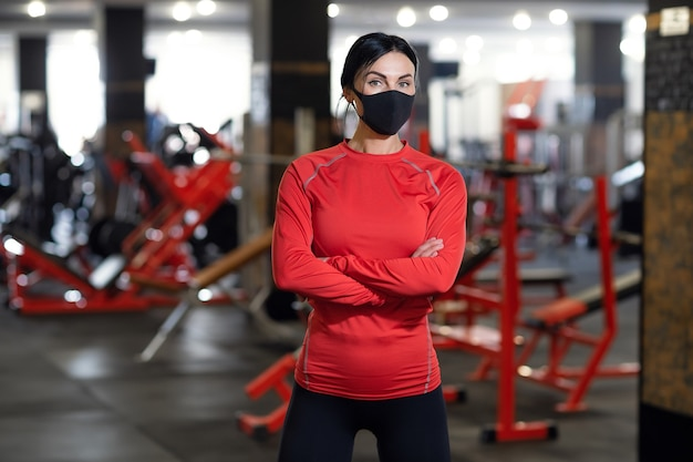 Coronavirus covid-19 prevention, fitness girl with a medical mask posing in gym