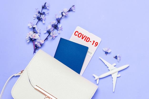コロナウイルスcovid-19。コロナウイルスの蔓延による旅行禁止。女性のハンドバッグ、アクセサリー、パスポート、チェリーの小枝