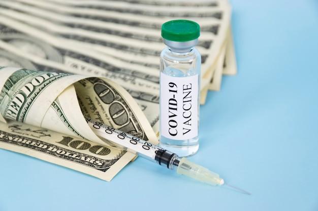 Стакан для вакцины против коронавируса covid-19, шприц и деньги