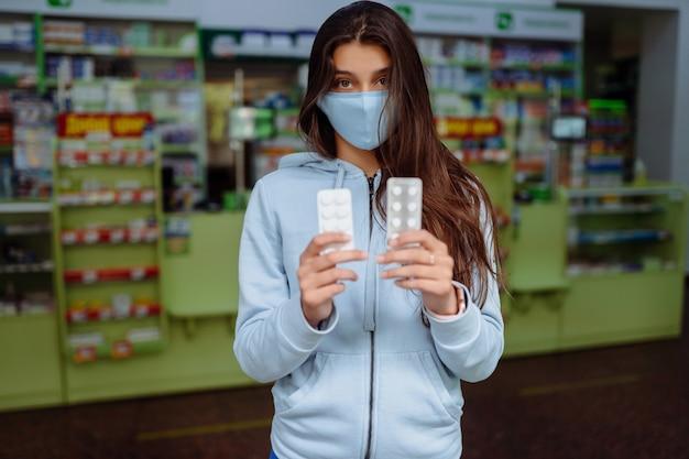 코로나 바이러스. 코로나 19. 여자는 알약, 비타민 또는 알약을 손에 들고 보여줍니다. 비타민 또는 알약. 건강 및 치료 개념.